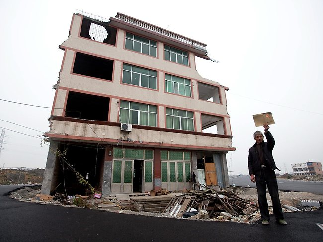 Refusenik: Luo Baogen stands next to his house in the middle of a newly built road in Zhejiang province. (AP Photo)