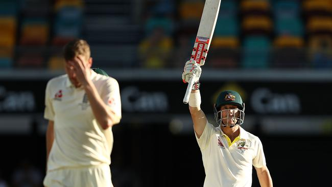 David Warner of Australia celebrates after reaching his half century as Jake Ball of England walks back to his mark.