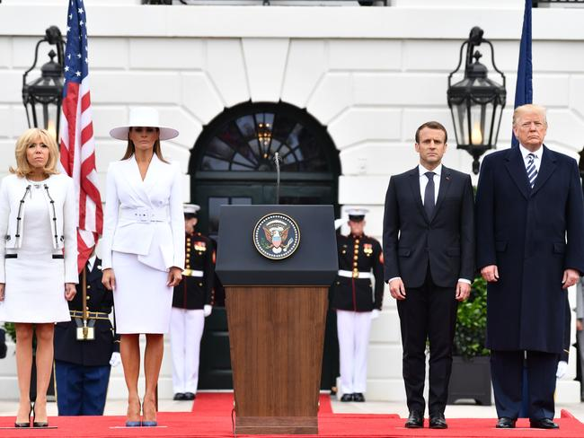 Melania Trump looked serious in white, beside an equally sober Brigitte Macron and their presidential husbands. Picture: AFP/Nicholas Kamm