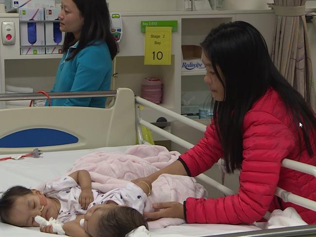 Nima and Dawa with their mother as they bravely prepare for their surgery earlier today. Source: RCH Melbourne Studio.