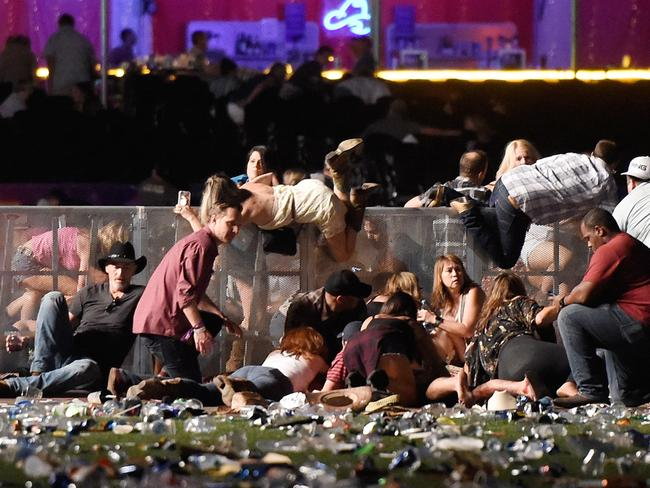 People climb over walls to shelter from the gunman. Picture: David Becker/Getty Images/AFP