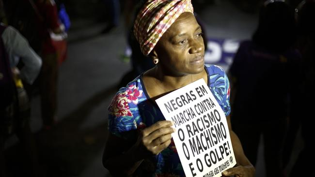 A woman holds a sign reading 'Black women march against racism, male chauvinism and the coup' during a protest against conservative Brazilian politicians – including Jair Bolsonaro.
