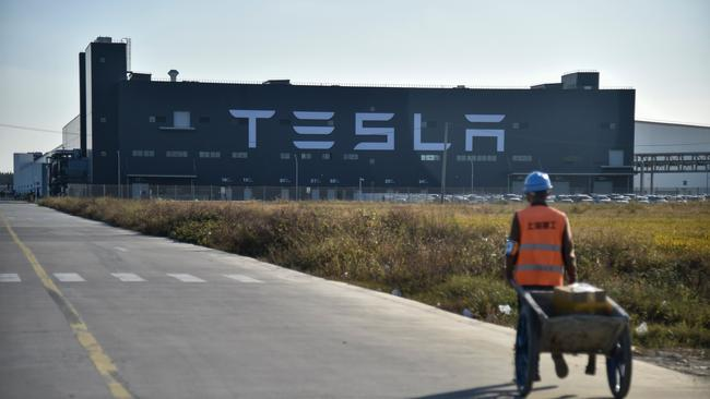 A worker walks on a road next to the new Tesla factory built in Shanghai. (Photo by HECTOR RETAMAL / AFP)