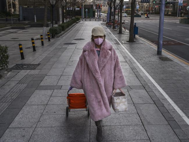 A pedestrian wears a protective mask walking in an empty area of Beijing. Picture: Kevin Frayer/Getty Images.