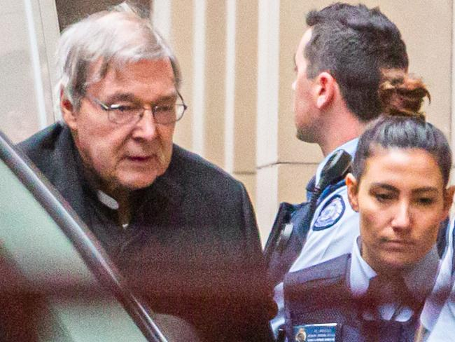Cardinal George Pell is escorted into the Supreme Court of Victoria yesterday. Picture: Asanka Brendon Ratnayake/AFP