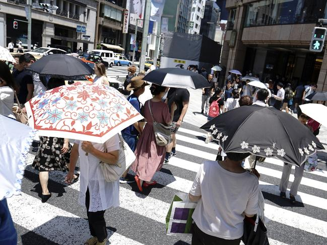 People under parasols walk on a pedestrian crossing in Tokyo. Picture: AP