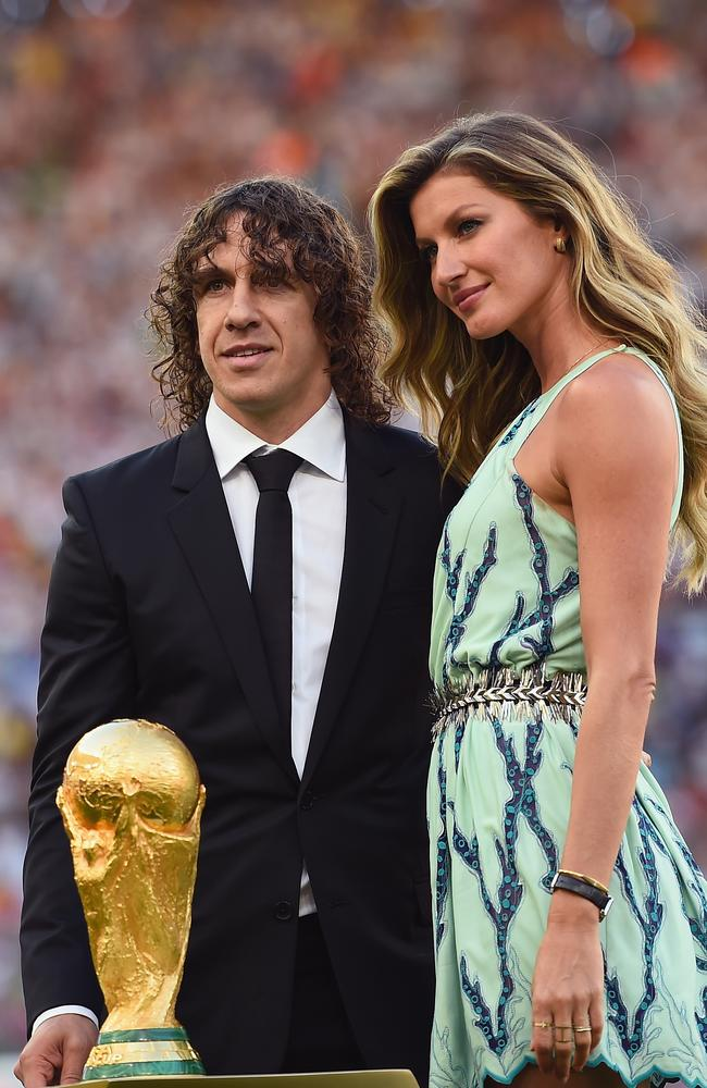 Former Spanish international Carles Puyol and model Gisele Bündchen present the World Cup trophy.