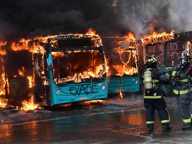 Chilean firefighters extinguish burning buses during clashes between protesters and the riot police in Santiago. Picture: AFP