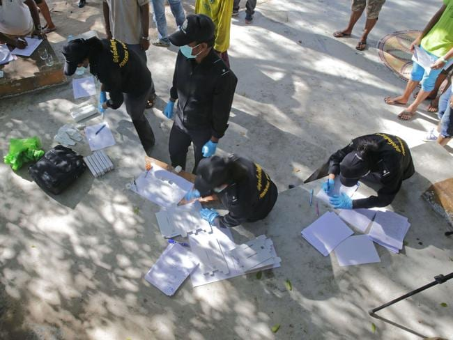 Manhunt ... Thai policemen conduct DNA tests on staff from two beachside bars. Picture: AFP