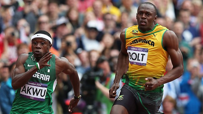 Jamaica's Usain Bolt powers around the turn in his heat of the 200m. Noah Akwu of Nigeria is on his outside. Picture: Phil Hillyard