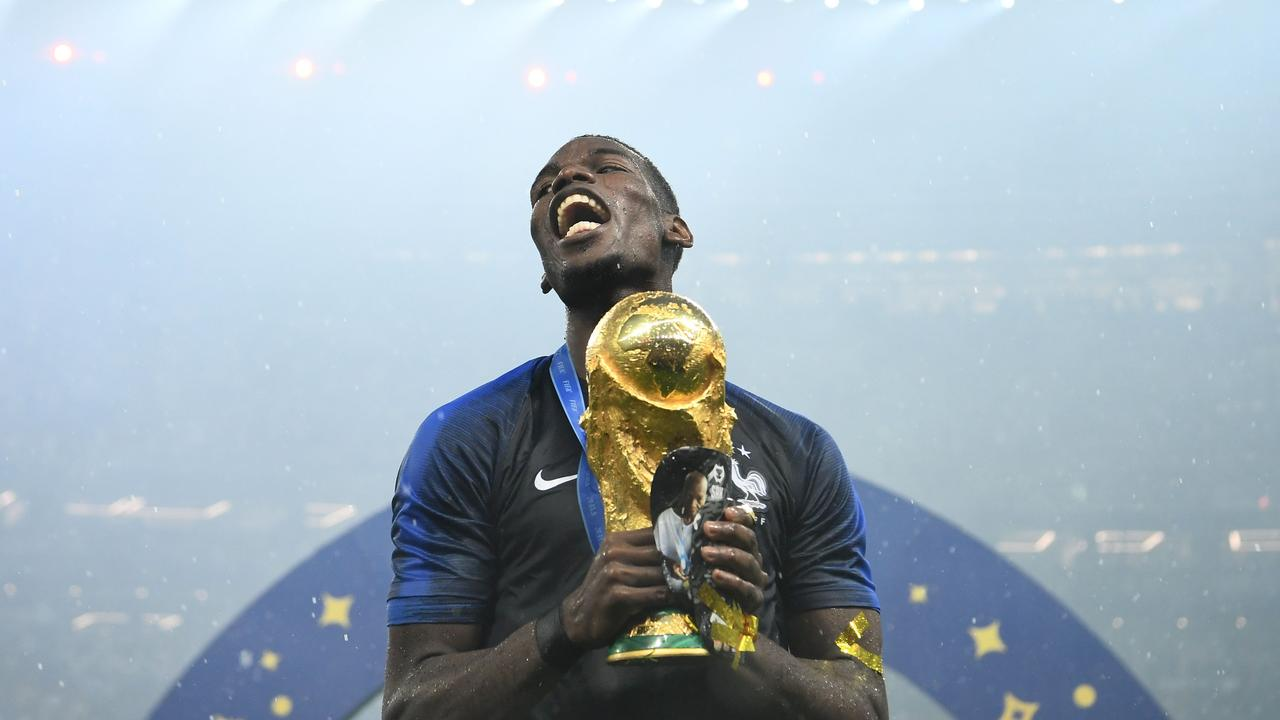 France's midfielder Paul Pogba celebrates with the World Cup trophy.