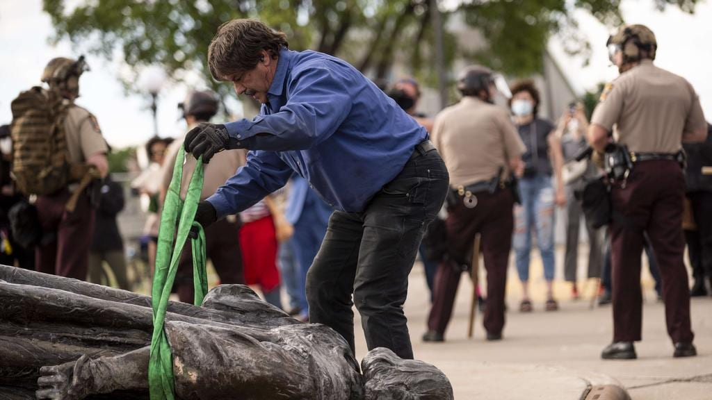 A statue of Christopher Columbus, toppled to the ground by protesters, is loaded onto a truck on the grounds of the State Capitol in St Paul, Minnesota. Picture: Stephen Maturen/Getty Images/AFP