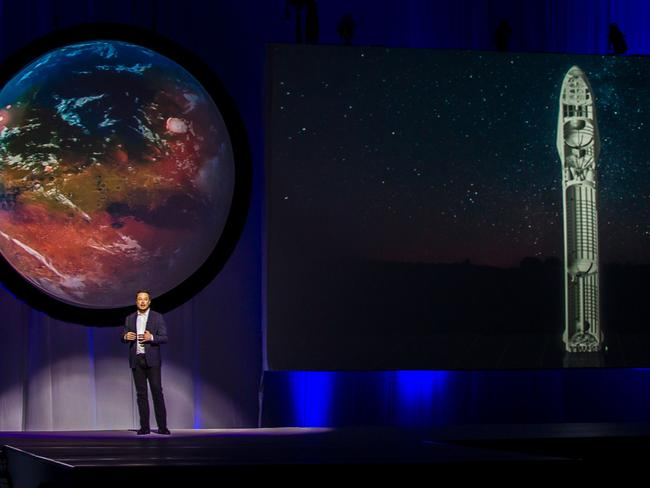Elon Musk makes a presentation with the image of a terraformed Mars and a cutaway of his Starship design behind him. Picture: AFP