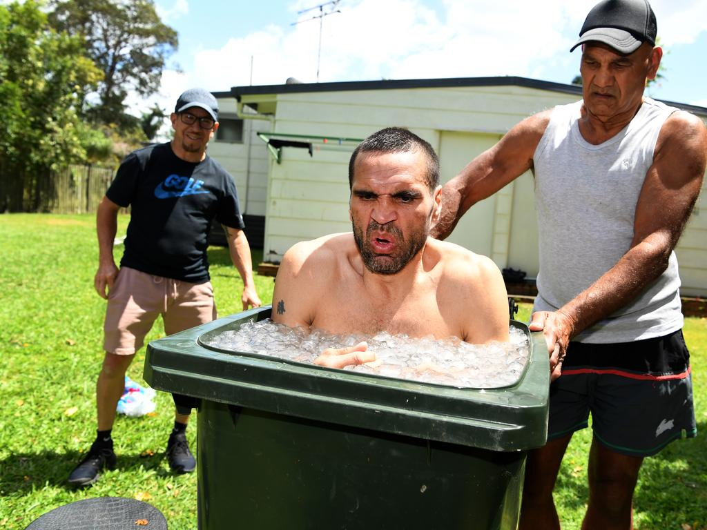 Australian boxer Anthony Mundine, helped by his father Tony, takes an ice bath inside a garbage bin after a training session in Brisbane.