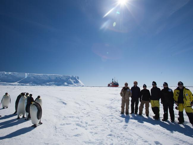 Members of the Mawson's Huts Foundation expedition and emperor penguins on sea ice at Commonwealth Bay last December. Picture: DAVID KILLICK