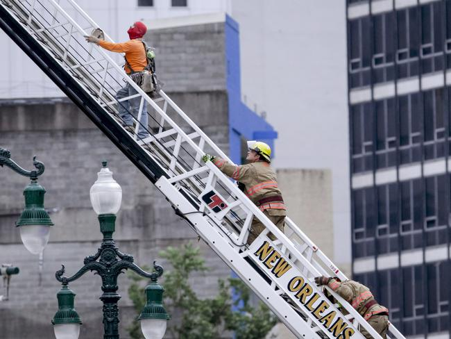 A rescue worker, left, and a firefighter look up at the damaged building. An unstable crane over 80-metres tall is looming over the site and hampering rescue efforts. Picture: AP