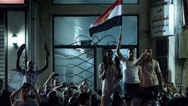 """Egyptian protesters gather on a street near the US Consulate where US Secretary of State Hillary Clinton attended a flag-raising ceremony. The protesters threw shoes, tomatoes and taunted Clinton with chants of """"Monica"""". Pic: AFP"""