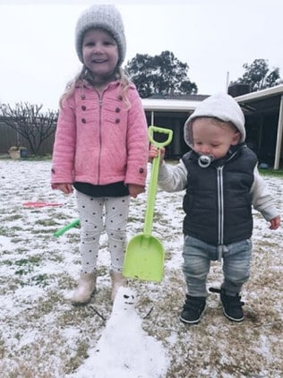 Willow and Max make a snowman out of hail and sleet caused by a cold snap. Picture: Chloe Bartley