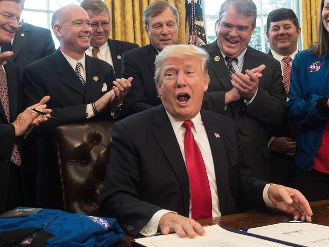 US President Donald Trump signs a bill increasing NASA's funding in 2017. He's reminded NASA he wants them to spend the money on getting to Mars. Picture: AFP