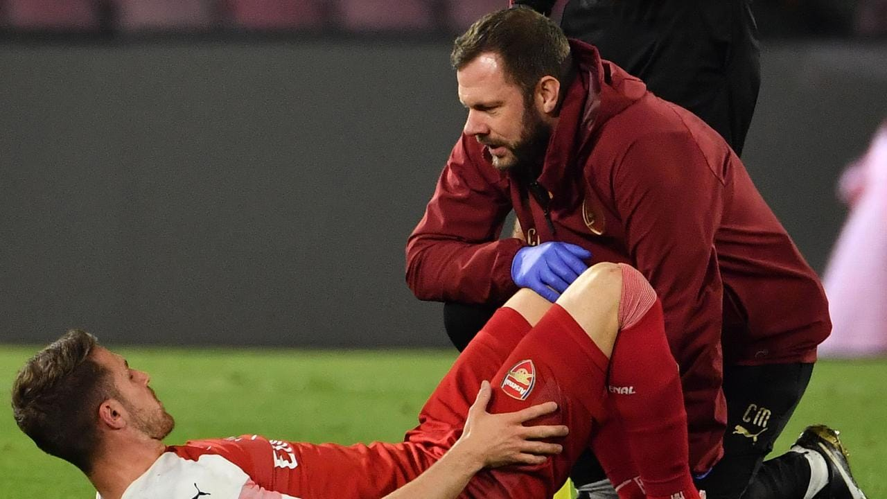 A staff medic tends to Arsenal's Welsh midfielder Aaron Ramsey after he was injured