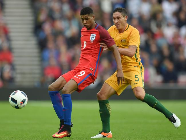 Marcus Rashford (L) vies for the ball against Australia's Mark Milligan.