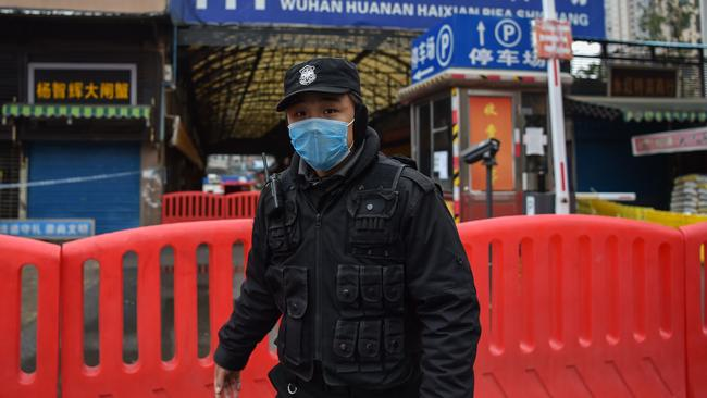A police officer stands guard outside of Huanan Seafood Wholesale market. Picture: Hector Retamal/AFP.