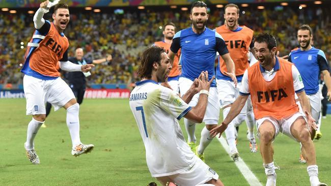 Greece's forward Georgios Samaras (C) celebrates with teammates after scoring a penalty.