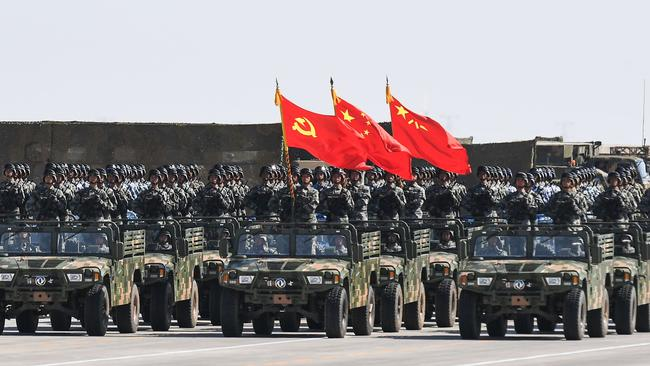Chinese soldiers carry the flags of the Communist Party, the state, and the People's Liberation Army during a military parade in July.