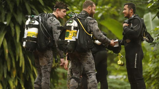 Australian Federal Police and Defence Force personnel talk with a Thai diver after the 12 boys and their soccer coach were found alive in a flooded cave in Mae Sai, Chiang Rai province, northern Thailand. Picture: Sakchai Lalit/AP