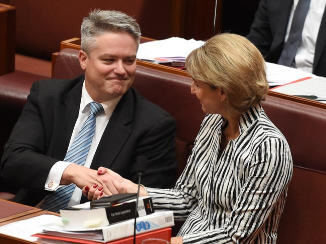 Finance Minister Mathias Cormann congratulates Employment Minister Michaelia Cash after the Registered Organisations Bill passes the Senate. Picture: AAP Image/Mick Tsikas
