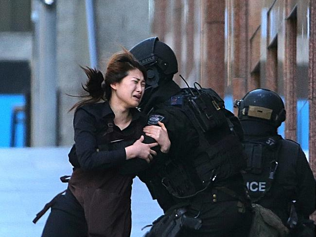 The image of a cafe worker running into the arms of police went around the world. Picture: AP / Rob Griffith