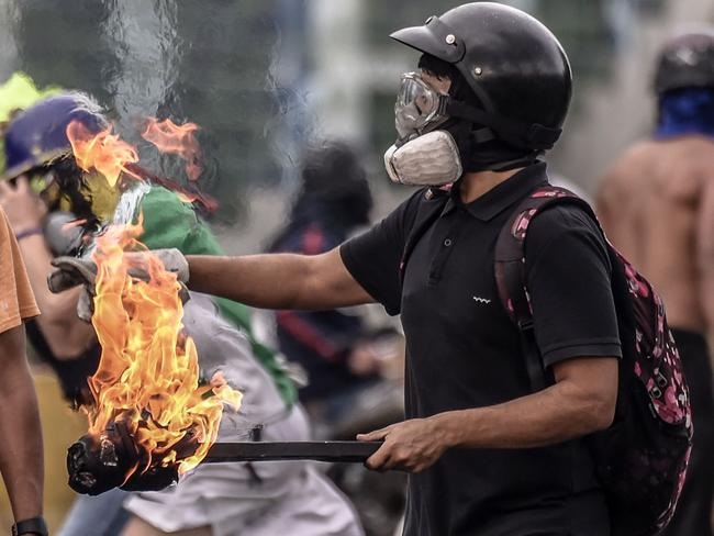 An opposition activist clashes with the police at the Francisco de Miranda air force base during a demonstration against the government. Picture: AFP