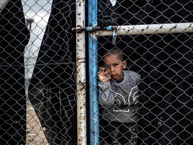 A child waits behind a wire fence door in al-Hawl camp. Picture: Delil Souleiman/AFP