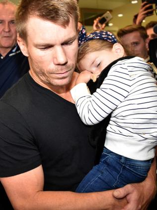 David Warner was sombre as he left the airport with his wife and two kids after arriving back in Sydney. Picture: Peter Parks/AFP