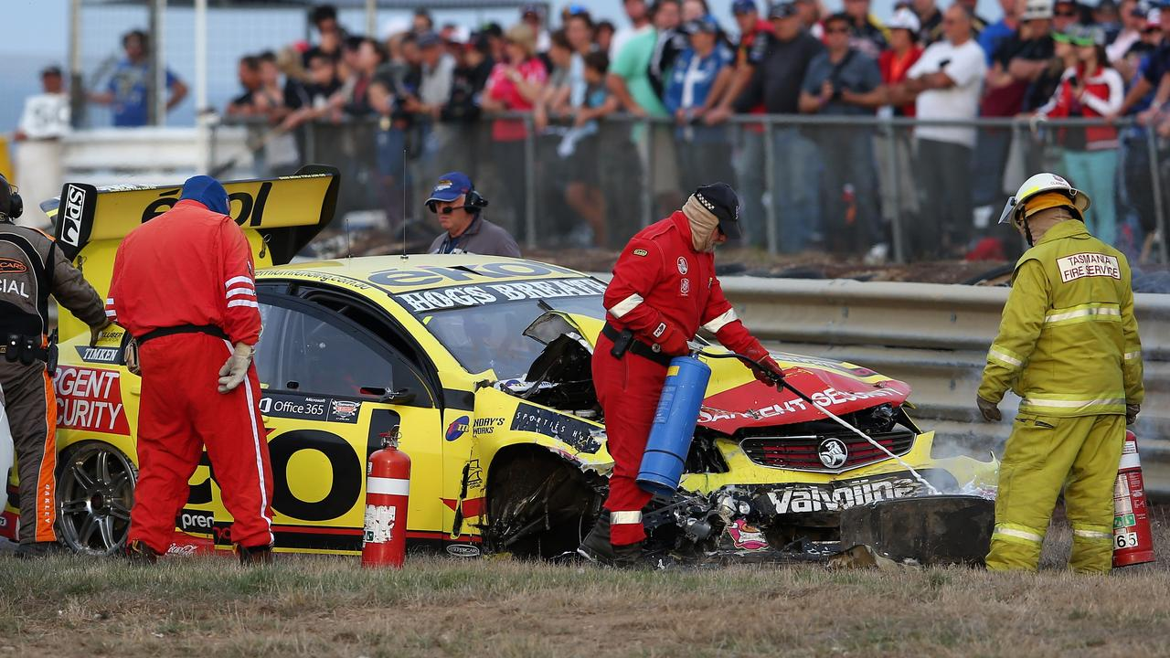 Marshals inspect the wrecked car of Scott Pye at Symmons Plains in 2013.