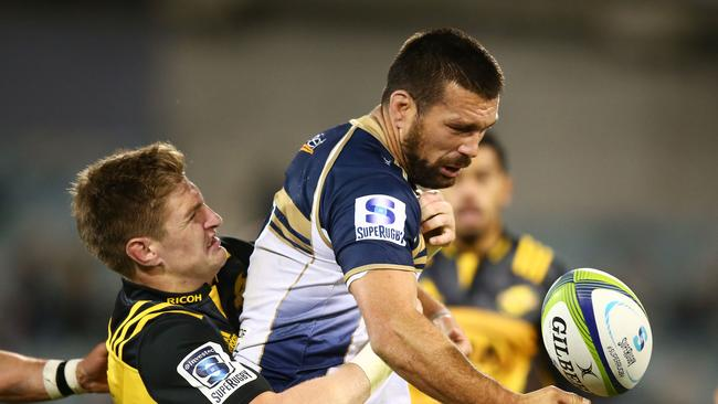 Chris Alcock of the Brumbies loses the ball in a tackle by Jordie Barrett of the Hurricanes.