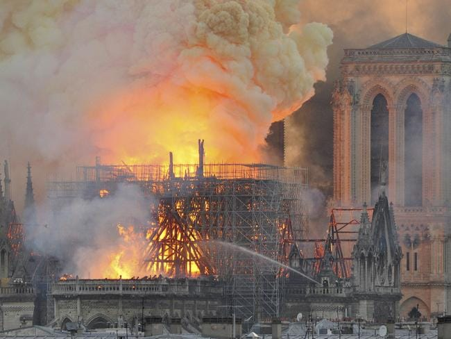 Flames and smoke rise from the blaze after the spired toppled over on Notre Dame cathedral yesterday. Picture: Thierry Mallet