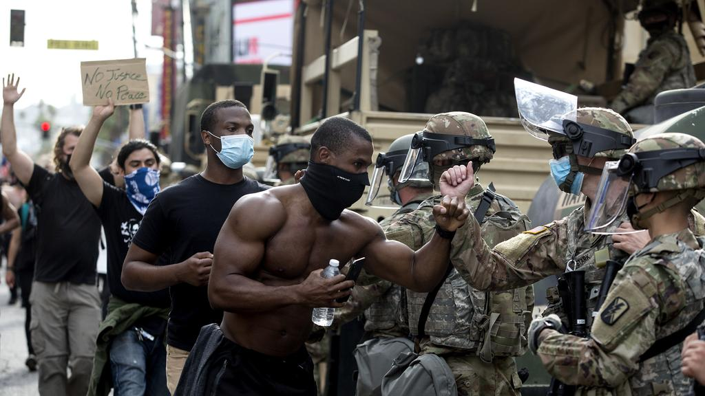 Demonstrators greet members of the National Guard as they march along Hollywood Boulevard, Tuesday in the Hollywood section of Los Angeles. Picture: AP/Ringo HW Chiu