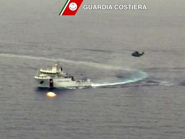 Rescue mission ... a helicopter and a ship take part in a rescue operation off the coast of Sicily. Picture: AFP/Guardia Costiera