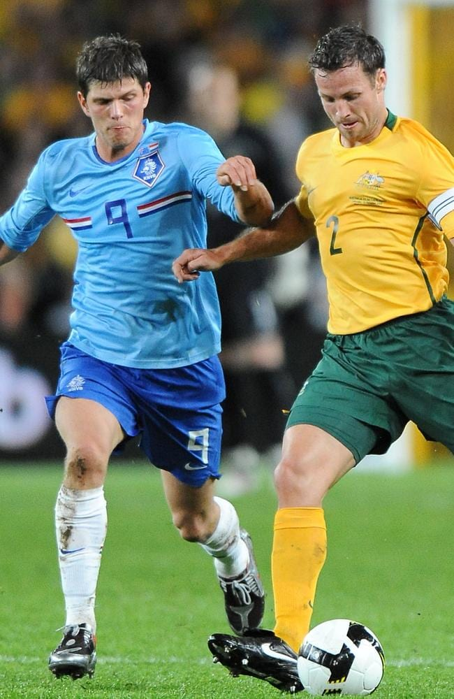 Socceroos captain Lucas Neill (R) clashes with Klaas Jan Huntelaar (L).