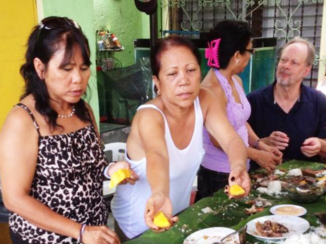 Las Vegas shooter Stephen Paddock (right, black shirt) sharing a meal with Marilou Danley's family in Manila in 2013. Picture: Supplied
