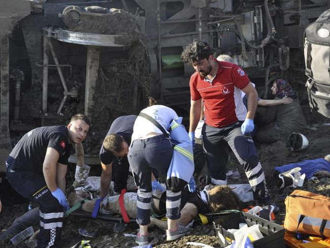 Emergency services rescue victims from overturned train cars near a village in Turkey where at least 10 people were killed and 73 injured. Picture: Mehmet Yirun/DHA-Depo/AP