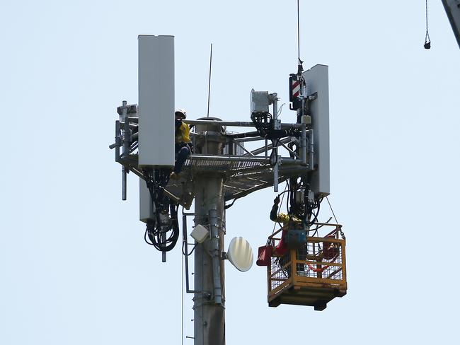 Sub-contractors completing maintenance work on a mobile phone tower used by internet companies for telecommunications service. Picture: Brendan Radke.