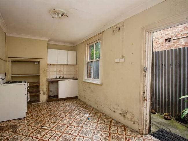 The kitchen at 46 Boronia Street, Redfern shows a mouldy and uninhabitable house with a corrugated iron fence. Picture: realestate.com.au.