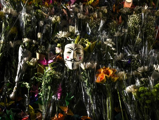 A Guy Fawkes mask is left among flowers during a prayer rally in Tamar Park in Hong Kong. Picture: AFP