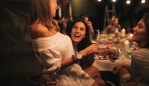 Photo of a cheerful friends during the dinner party in an outdoors bistro cheering, toasting and laughing