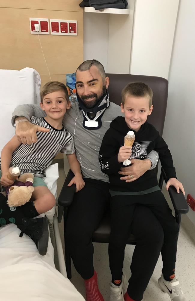 Mr Lewis is undergoing intensive rehab therapy. He is pictured here with sons Connor, left, and Oscar, right, at Royal North Shore hospital.