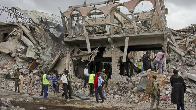 Somali security forces and others gather and search for bodies near destroyed buildings at the scene of Saturday's blast in Mogadishu, Somalia, on October 15. Picture: Farah Abdi Warsameh/AP