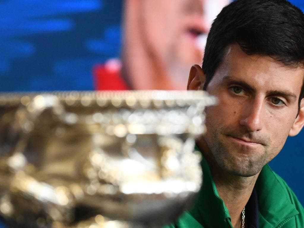 Serbia's Novak Djokovic looks at the Norman Brookes Challenge Cup trophy during a press conference after beating Austria's Dominic Thiem in their men's singles final match on day fourteen of the Australian Open tennis tournament in Melbourne on February 3, 2020. (Photo by John DONEGAN / AFP) / IMAGE RESTRICTED TO EDITORIAL USE - STRICTLY NO COMMERCIAL USE
