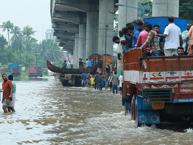 Indian commuters travel in a truck to a safer place as flood waters ravaged Kerala. Picture: AFP
